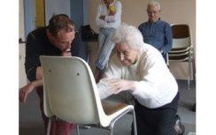 Dame âgée qui s'aide d'une chaise pour se relever